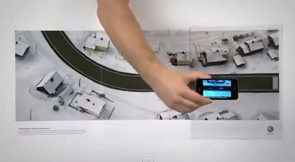 Interactive print ad by Volkswagon with three-page spread simulating a car test drive via smartphone.